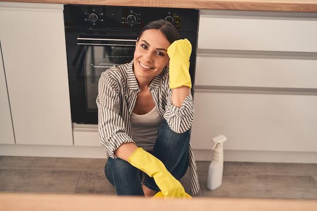 Bastante joven manteniendo una sonrisa en su rostro mientras está sentada en el suelo después de limpiar la estufa del horno