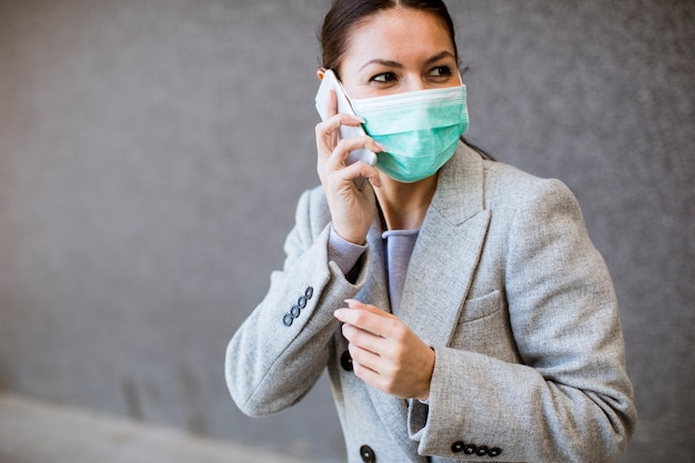 Bastante joven con máscara facial protectora en la calle
