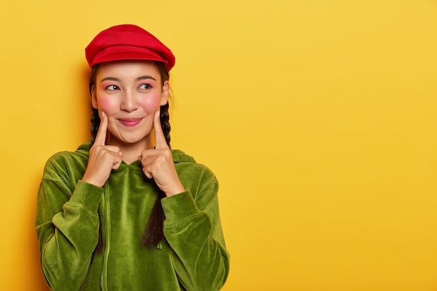 Bastante joven modelo asiática mantiene ambos dedos índice en las mejillas, se ve con expresión soñadora a un lado, tiene un mínimo de maquillaje, usa boina roja, sudadera con capucha de terciopelo verde
