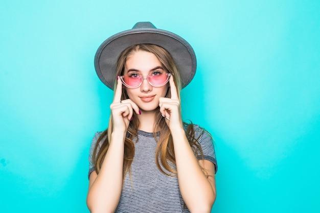 Bastante joven modelo en camiseta de moda, sombrero y gafas transparentes aisladas sobre fondo verde