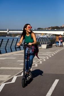 Bastante joven montando un scooter eléctrico en la calle