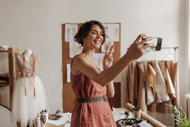 Bastante joven morena de pelo corto en vestido rojo de lino con cinturón negro sonríe, toma selfie, muestra el signo de la paz y posa en la oficina del diseñador de moda