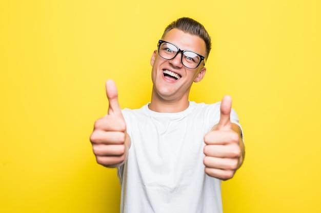 Bastante joven muestra los pulgares para arriba signo vestido con camiseta blanca y gafas transparentes