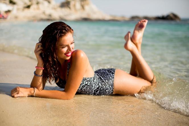Bastante joven mujer acostada en la playa
