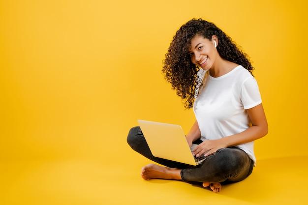 Bastante joven mujer africana negra sentada con laptop y earpods aislados sobre amarillo