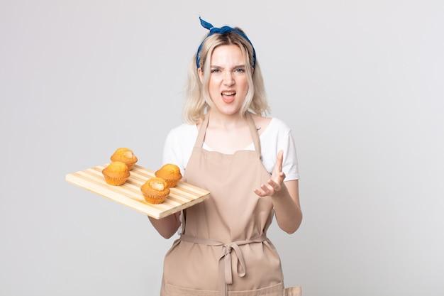 Bastante joven mujer albina que parece enojada, molesta y frustrada con una bandeja de muffins