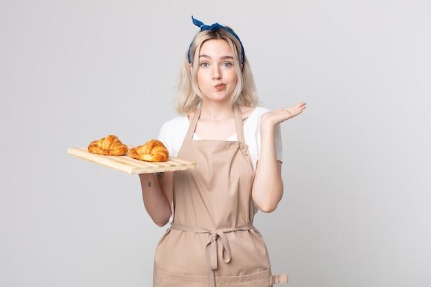 Bastante joven mujer albina que se siente desconcertado y confundido y dudando con una bandeja de croissants