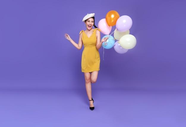 Bastante joven mujer asiática en la fiesta de celebración con globo de colores corriendo y sonreír. feliz año nuevo o víspera de cumpleaños celebrando el concepto en la pared de color púrpura brillante.