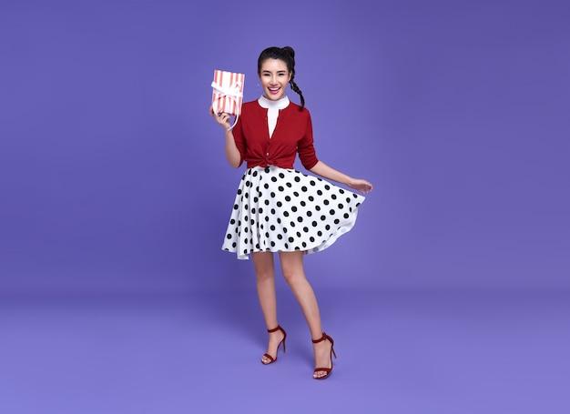 Bastante joven mujer asiática en lindo atuendo casual sosteniendo rojo se presenta bailando alegremente. feliz año nuevo o víspera de cumpleaños celebrando el concepto. en la pared de color púrpura brillante.