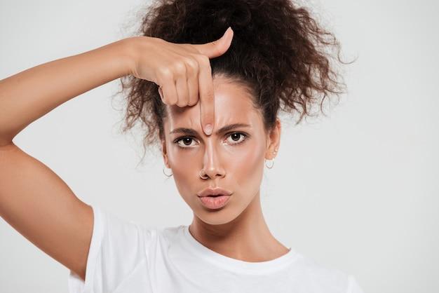 Bastante joven mujer con cabello rizado con el dedo índice