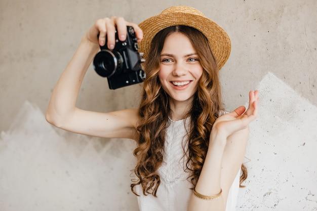 Bastante joven mujer feliz sonriente vistiendo blusa blanca sentada contra la pared con sombrero de paja