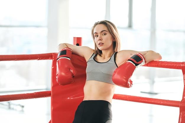 Bastante joven mujer en guantes de boxeo rojos y chándal mirándote mientras se inclina contra las barras del ring en el gimnasio