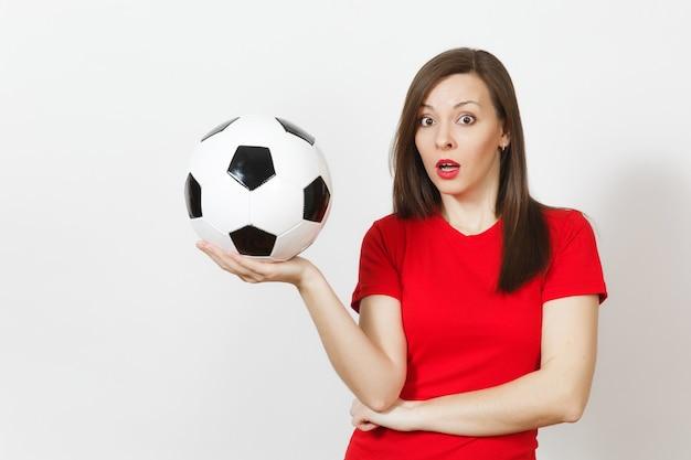 Bastante joven mujer molesta triste europea, aficionado al fútbol o jugador en uniforme rojo tiene balón de fútbol, se preocupa por perder equipo aislado sobre fondo blanco. deporte, jugar al fútbol, concepto de estilo de vida.