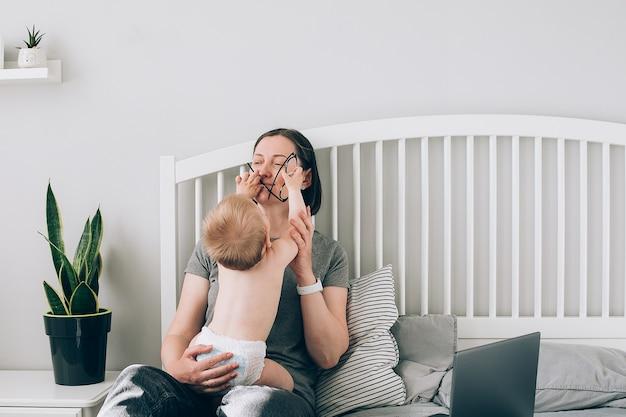 Bastante joven mujer morena con portátil en casa, tomando un descanso para jugar con el bebé. momento auténtico, paternidad, concepto de maternidad