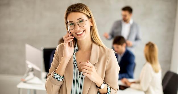 Bastante joven mujer de negocios de pie en la oficina y demandando teléfono móvil frente a su equipo