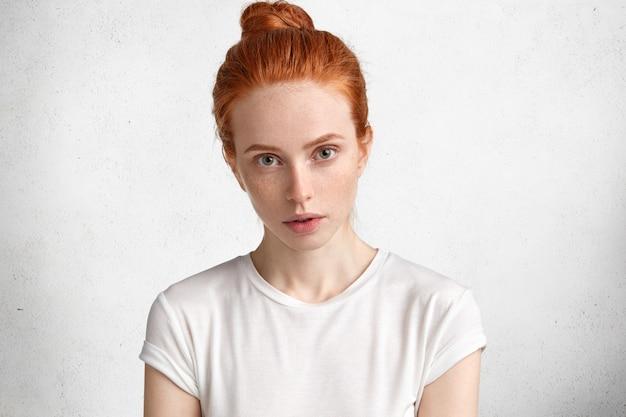 Bastante joven mujer pelirroja en camiseta casual, vestida con camiseta casual, mira con seriedad y confianza a la cámara, tiene un aspecto misterioso
