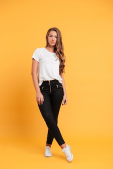 Bastante joven mujer de pie y posando aislado sobre pared amarilla