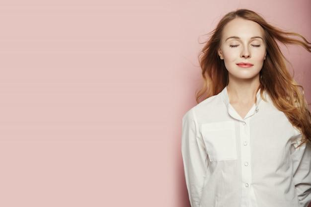 Bastante joven mujer posando sobre fondo rosa
