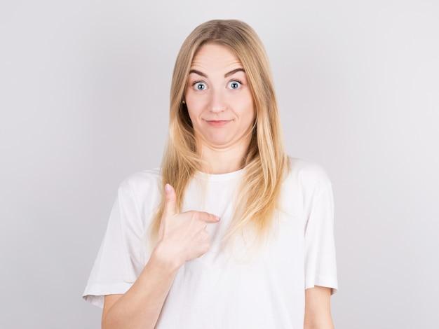 Bastante joven mujer que se siente confundida, perpleja e insegura, señalando a sí misma preguntándose y preguntando quién, yo