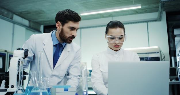 Bastante joven mujer de raza caucásica en gafas trabajando en el laboratorio y haciendo algunas pruebas en el tubo con líquido, luego tocando en la computadora portátil.