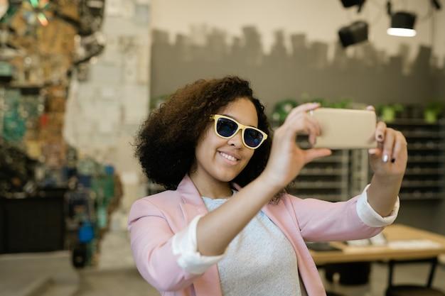 Bastante joven mujer de raza mixta en gafas de sol y elegante casual mirando en el teléfono inteligente mientras hace selfie