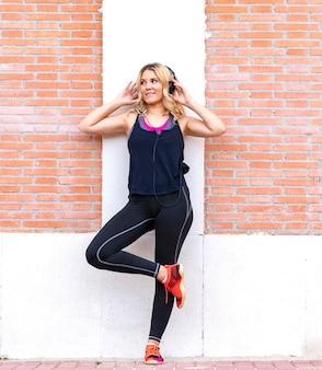 Bastante joven mujer rubia escuchando música con cascos y ropa deportiva en una pared.