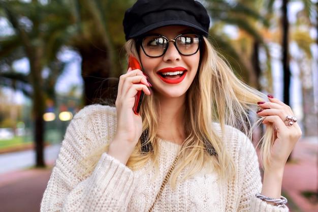 Bastante joven mujer rubia habla por su teléfono, ropa casual elegante, sombrero, suéter y gafas transparentes, emociones positivas, palmeras alrededor.