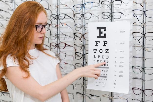 Bastante joven mujer señalando la carta en la tabla de snellen en la tienda de óptica