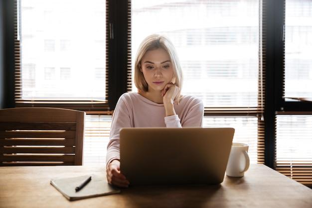 Bastante joven mujer sentada cerca del café mientras trabaja con el portátil