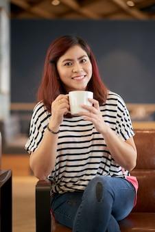 Bastante joven mujer tomando café
