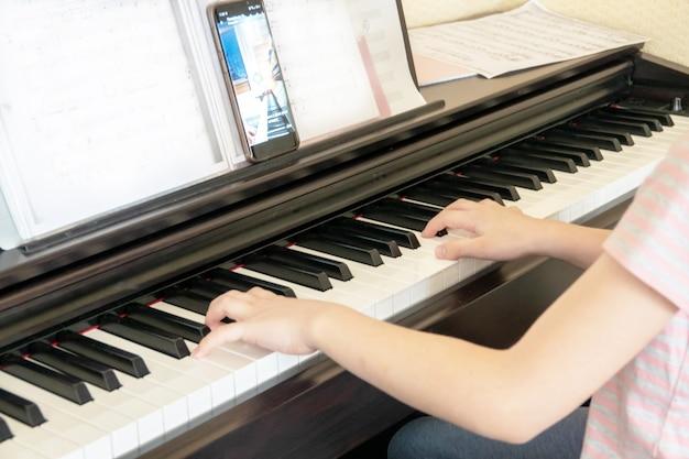 Bastante joven músico tocando el piano digital clásico en casa durante la clase en línea en casa, distancia social durante la cuarentena, autoaislamiento, concepto de educación en línea