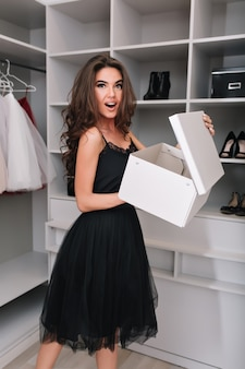 Bastante joven, niña felizmente sorprendida en un bonito armario con caja de zapatos nuevos, compró calzado nuevo. ella tiene cabello castaño largo y rizado, con un vestido negro glamoroso.