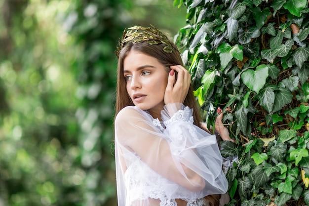 Bastante joven novia en ropa interior blanca y corona de oro plantea en un jardín verde