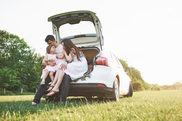 Bastante joven pareja casada y su hija están descansando en la naturaleza. la madre, el padre y la niña están sentados en el maletero abierto