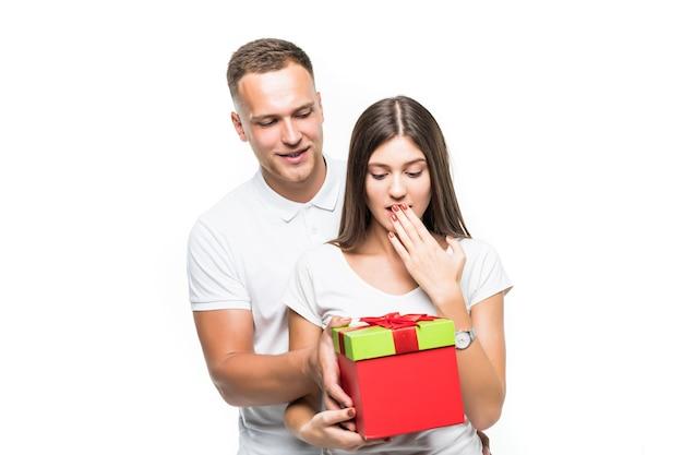 Bastante joven pareja da sorpresa a su dama caja de regalo roja aislado en blanco