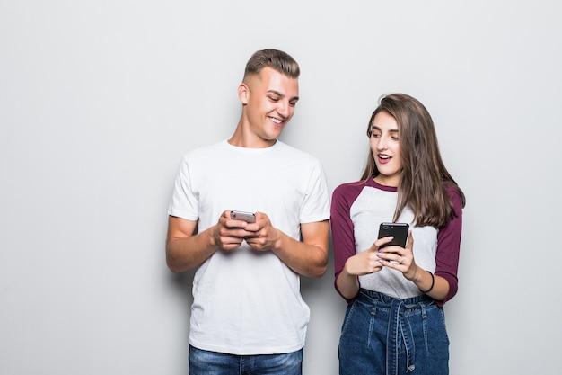 Bastante joven pareja guapo chico y chica mirando el uno al otro teléfono aislado en blanco