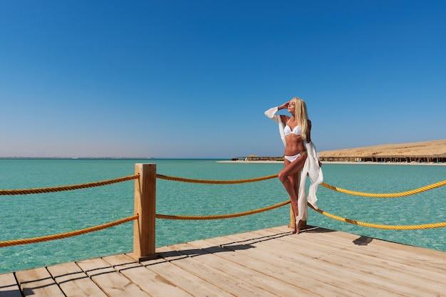 Bastante joven en pareo blanco de pie en el muelle cerca del mar