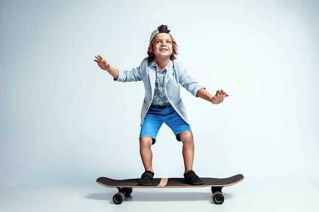 Bastante joven en patineta en ropa casual en blanco