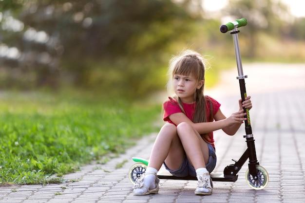 Bastante joven de pelo largo pensativo niño rubio niña en pantalones cortos y camiseta se sienta en scooter en la carretera vacía suburbio soleado