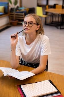 Bastante joven pensando en la biblioteca
