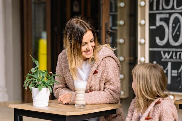 Bastante joven con pequeña hija encantadora vestida con suéteres calientes están sentados en la cafetería
