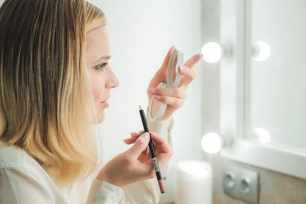 Bastante joven pinta labios mirando en espejo compacto