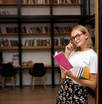 Bastante joven posando en la biblioteca