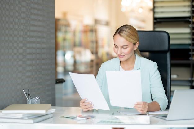 Bastante joven profesor elegante leyendo papeles de estudiantes mientras los revisa por escritorio
