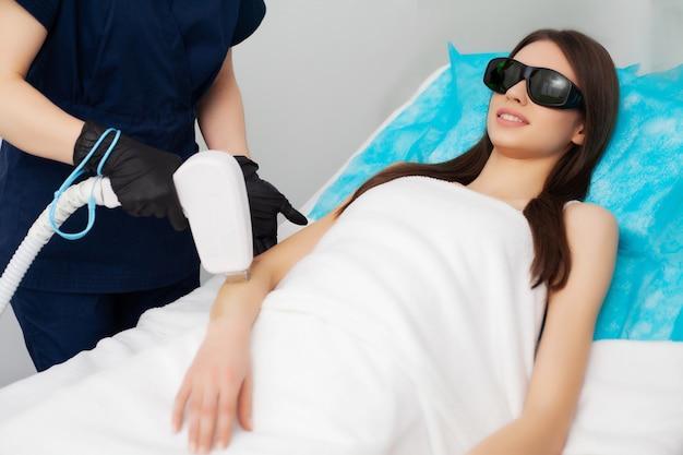 Bastante joven recibe depilación láser para piernas en salón de belleza