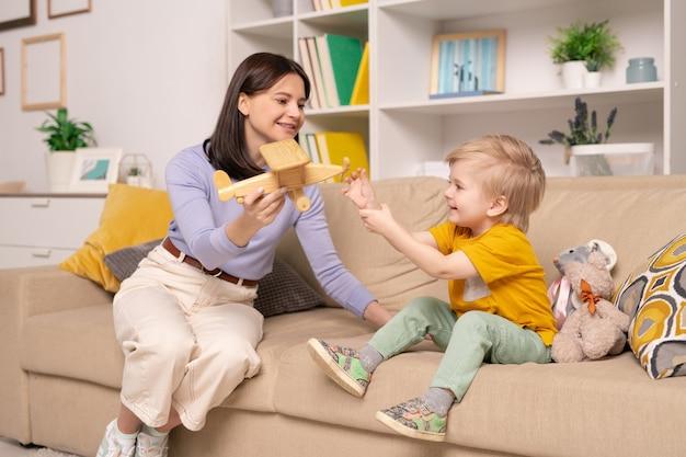 Bastante joven en ropa casual mostrando un avión de madera a su lindo hijo mientras juega con él en el sofá en el hogar