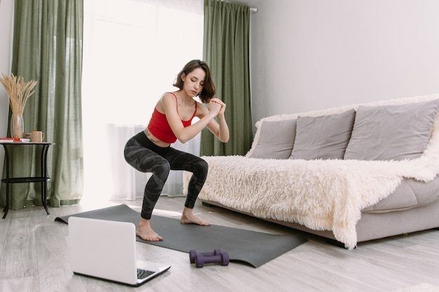 Bastante joven en ropa deportiva viendo videos en línea en la computadora portátil y haciendo ejercicios de fitness en casa. entrenamiento a distancia con entrenador personal, concepto de educación en línea