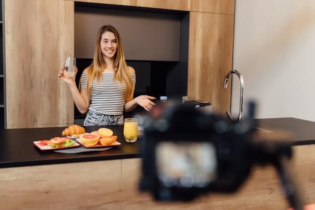 Bastante joven rubia blogger bebiendo agua en la cocina con comida sana en la mesa