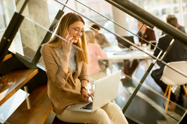 Bastante joven sentada en las escaleras con un portátil y usando un teléfono móvil en la oficina moderna frente a su equipo
