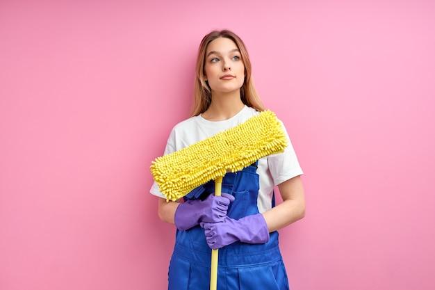 Bastante joven sirvienta caucásica va a limpiar el piso con un trapeador